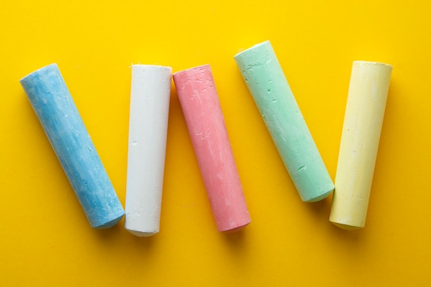 Colorful chalks over yellow background. education template. childhod, business and design.