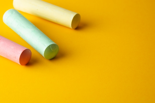 Colorful chalks over yellow background with copy space.