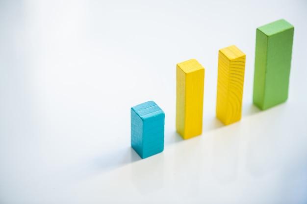 白い背景の上に並んで立っている青、黄色、緑の平らな木製のレンガで構成されたカラフルなチャート