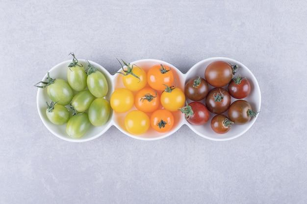 Pomodorini colorati in ciotole bianche.