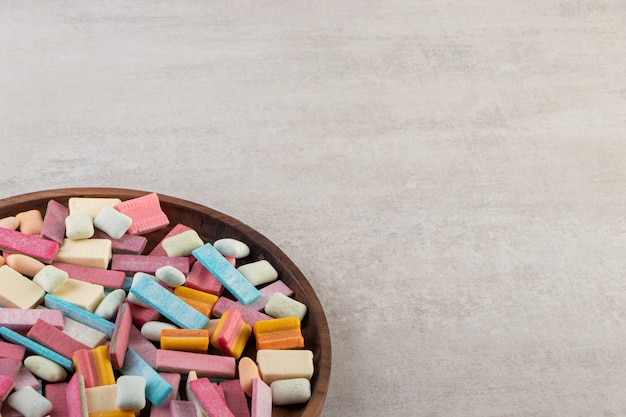 Colorful chewing gums placed on a stone table .