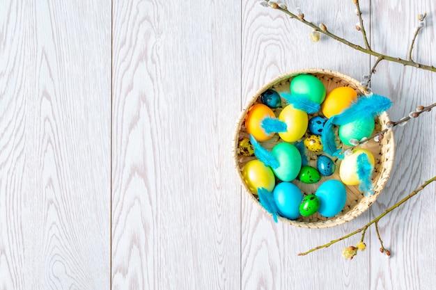 Красочные куриные и перепелиные пасхальные яйца в корзине с ветвями ивы