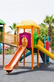 Красочная детская площадка в общественном парке в окружении зеленых деревьев.