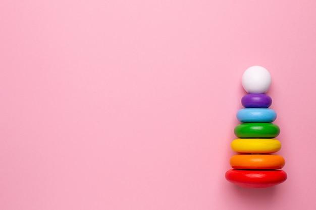 ピンクの背景にカラフルな子供用木製ピラミッド、コピースペースで幼児や赤ちゃんのトップビューのおもちゃ