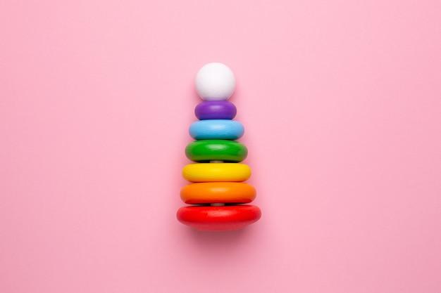 ピンクの背景にカラフルな子供用木製ピラミッド、幼児や赤ちゃんのためのおもちゃ上面図