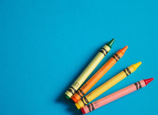 Colorful childs crayons on textured blue background with copy space to left