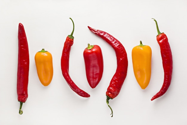 Colorful chili peppers on white wood