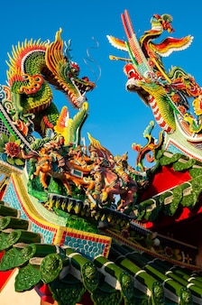 Colorful chinese figurines of dragons phoenix and some chinese warriors on top of green roof
