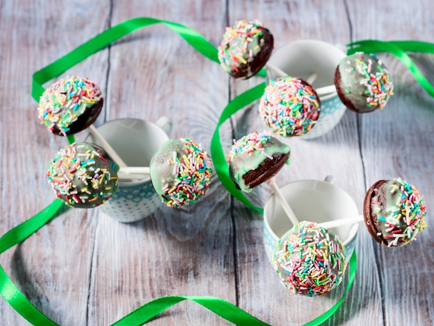 Colorful chocolate cake pops in cups