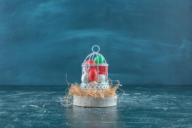 青い表面のボード上の乾いたわらの上の檻の中のカラフルなチョコレート