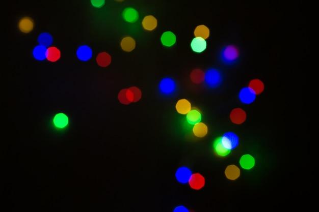 カラフルなクリスマスボケ、黒背景に隔離されています。クリスマスツリーライト背景。 ne