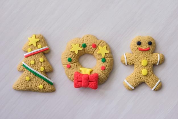 背景として木製のテーブルにカラフルなクリスマスクッキー
