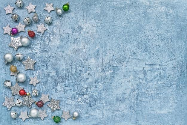 明るい青色の背景にカラフルなクリスマスの装飾。上面図、コピー