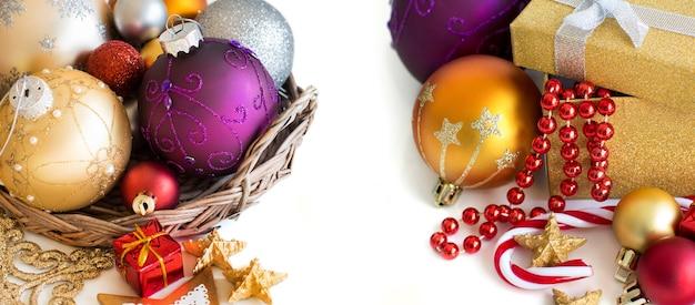 Красочные рождественские украшения - блесна, гирлянда и подарочная коробка на белом крупным планом