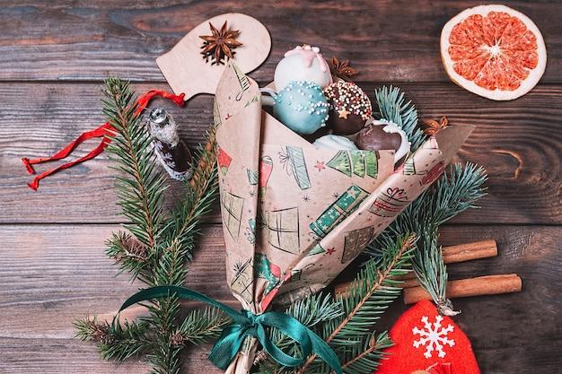 暗い木製の背景にカラフルなクリスマスの甘い食べ物