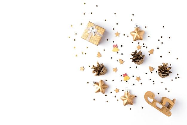Colorful christmas tree with new year`s decorations on white background. red gift box, candies, gold stars on holiday card. flat lay, top view