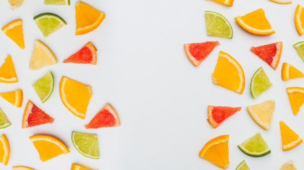 Colorful citrus fruits arranged with space between for writing text on white backdrop