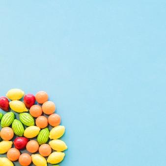 Colorful citrus fruits shape candies on blue background