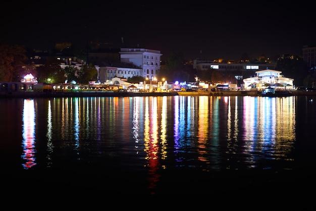 夜のカラフルな街のイルミネーション。海辺からの眺め