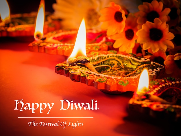 Colorful clay diya lamps lit with flowers for the hindu diwali festival.