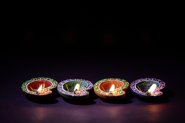 Colorful clay diya (lantern) lamps lit during diwali celebration. greetings card design indian hindu light festival called diwali.