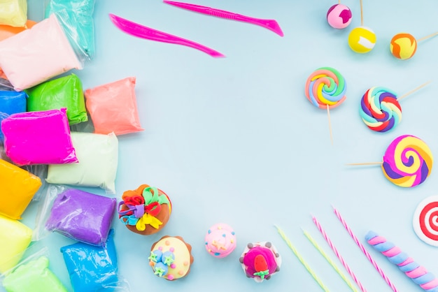 Colorful clay in plastic bag with fake cake and lollipop on blue background