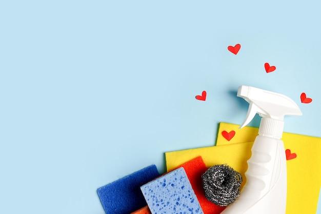 Красочный спрей бутылки чистящих средств с красными сердцами на синем фоне. концепция услуг по уборке. ранняя весенняя регулярная уборка.