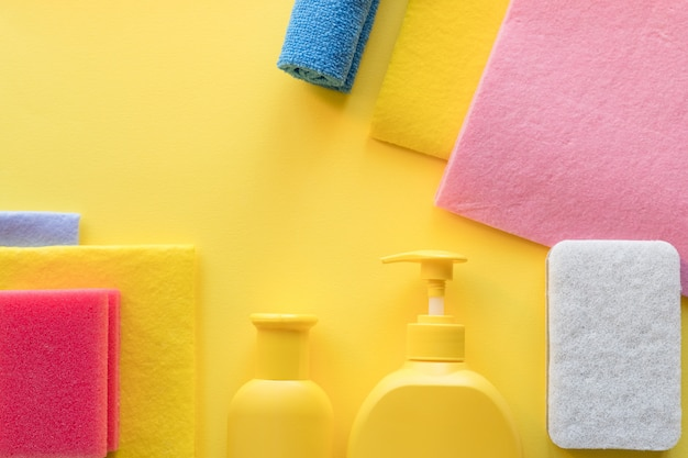 Colorful cleaning set for different surfaces in kitchen, bathroom and other rooms. empty place for text or logo on yellow background. cleaning service concept. cleaning items.regular clean up.