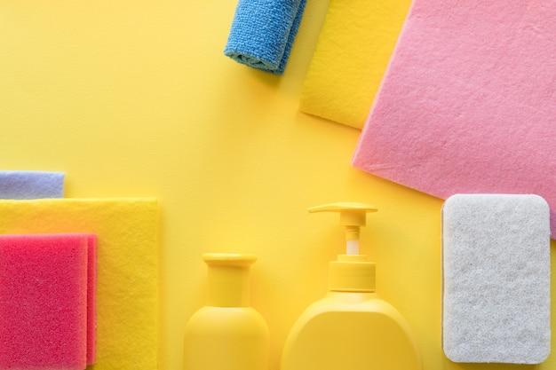 Красочный набор для чистки различных поверхностей на кухне, в ванной и других помещениях. пустое место для текста или логотипа на желтом фоне. концепция уборки. чистка предметов. регулярная уборка.