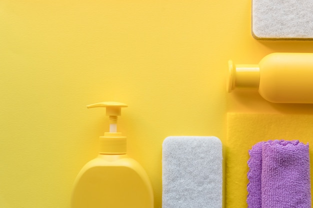 キッチン、バスルーム、その他の部屋のさまざまな表面用のカラフルなクリーニングセット。黄色の背景にテキストまたはロゴの空の場所。クリーニングサービスのコンセプト。アイテムのクリーニング。通常のクリーンアップ。