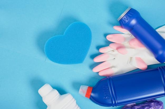 キッチン、バスルームのクリーニングサービス、春の大掃除のコンセプトのさまざまな表面に対応するカラフルなクリーニングセット。コピースペースブルーの背景スポンジ、手袋、洗剤ボトル
