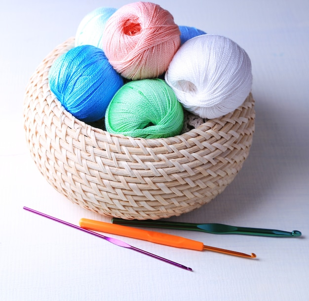 Colorful clews and crochet hooks in wicker basket on wooden surface