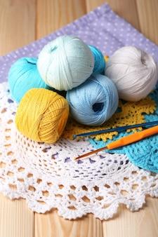 Красочные клубки, салфетки и крючки для вязания на деревянном столе