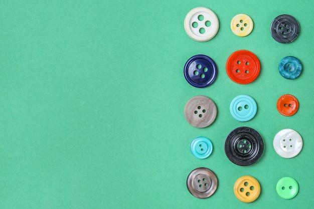 緑の背景にカラフルな布ボタン