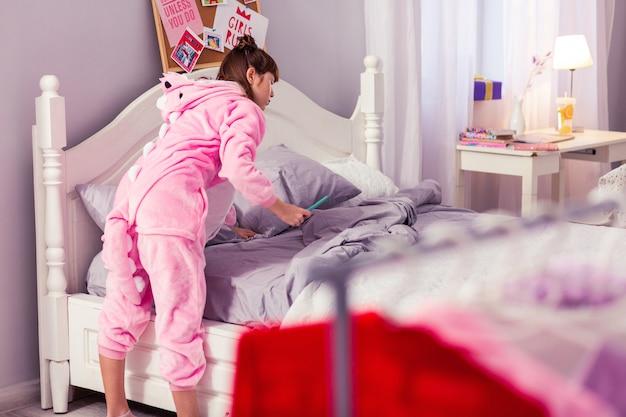 Красочная одежда. внимательная школьница стоит в полуположении, опираясь на кровать