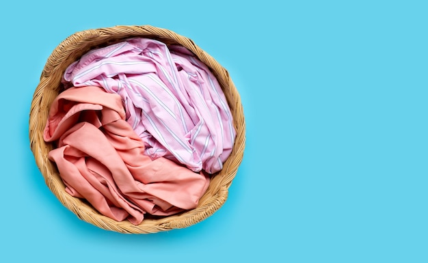 Colorful clothes in laundry basket on blue background. copy space