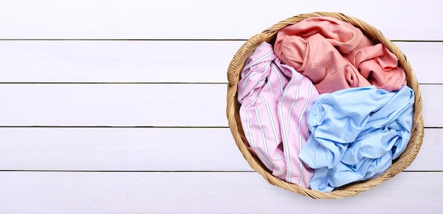 Colorful clothes in laundry basket on white wooden background. copy space