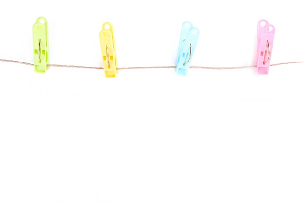 Colorful clothes pins on rope isolated on white