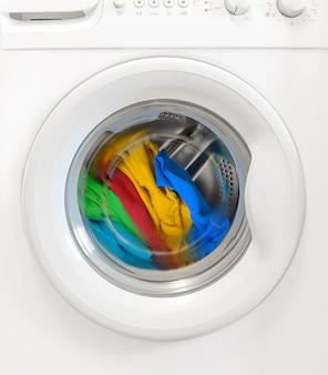洗濯機のタンクで回転するカラフルな服