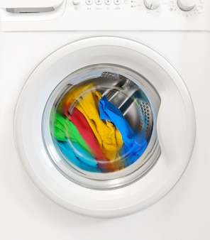 Colorful clothes rotating in washing machine tank