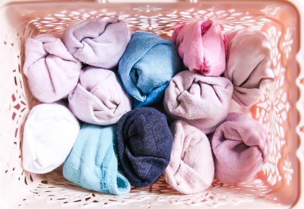 Вертикальное хранение красочной одежды в домашнем гардеробе. предметы одежды в коробке на мягком розовом фоне.