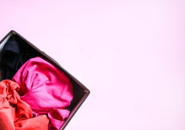Вертикальное хранение красочной одежды в домашнем гардеробе. предметы одежды в текстильной коробке на мягком розовом фоне.