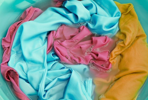 Colorful clothes in a wash basin close-up