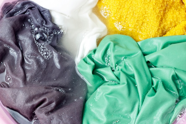 Colorful clothes washed with a basin with soap bubbles