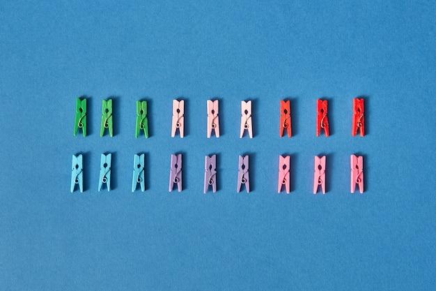 Разноцветные прищепки из двух рядов на синем с мягкими тенями и копией пространства. плоская планировка.