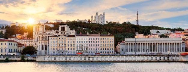 リヨンのソーヌ川の川岸から見た、ヴューリヨンとフルヴィエール大聖堂に沈むカラフルで曇りの夕日。