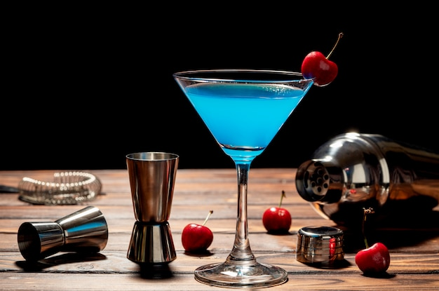 Colorful cocktail blue martini recipe with red cherry and bartender accessories on the wooden table