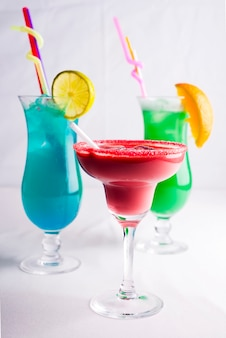 Colorful cocktails in glass on white background