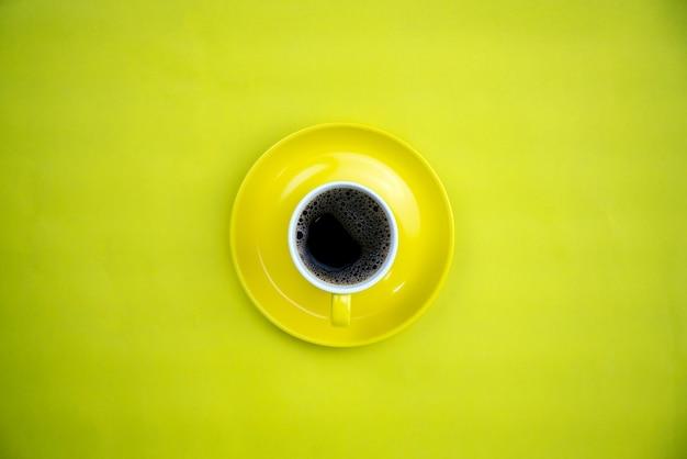 Красочная кофейная чашка на желтой бумажной предпосылке.