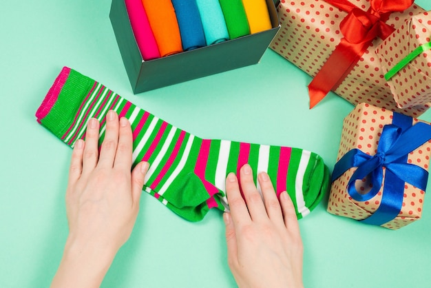 Colorful collection of cotton socks as a gift in woman hands